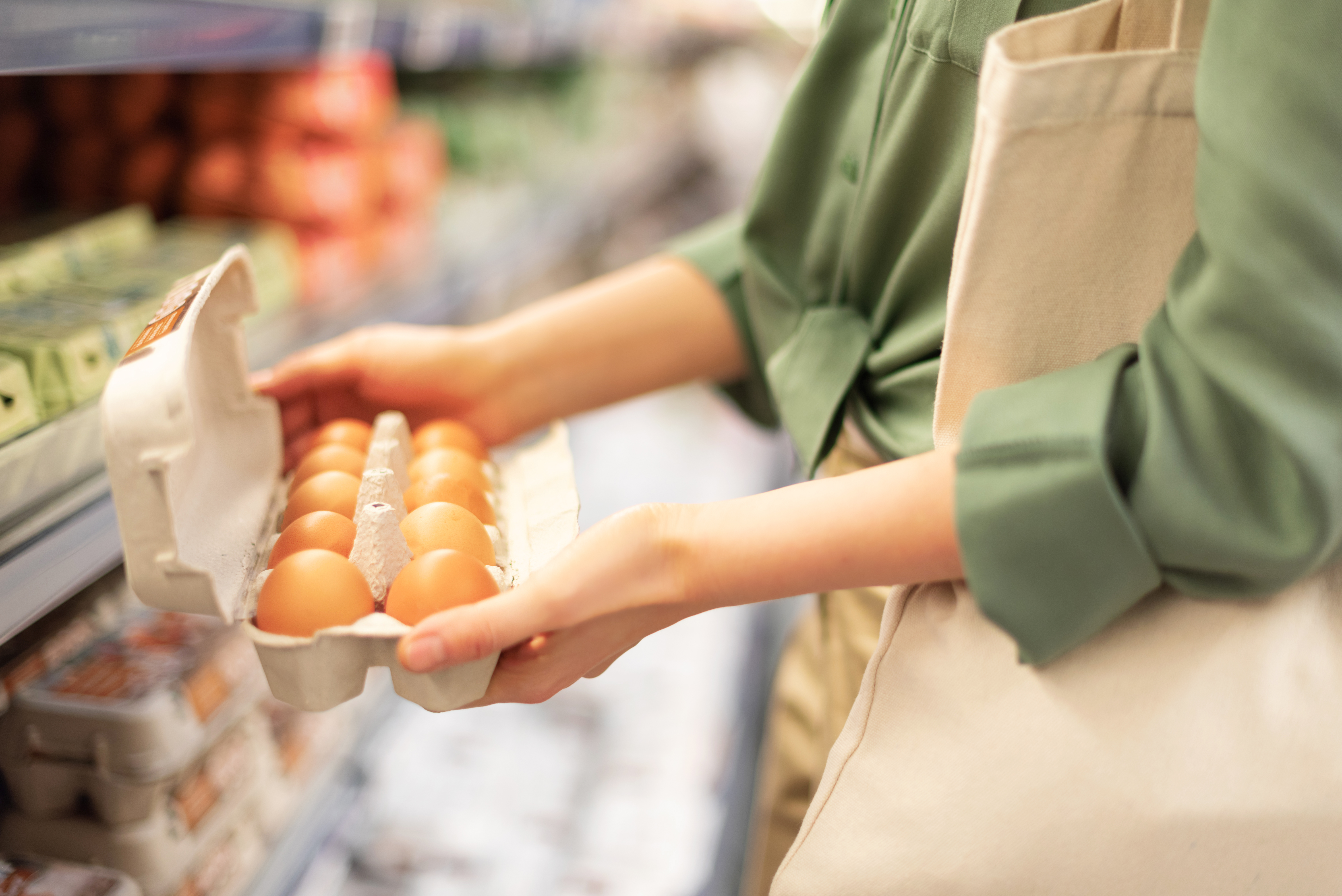 A girl is holding eggs package in hand